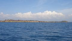 Landscape of the Tour des Ports - part of the iles de Chausey with afternoon cumulus building over the mainland