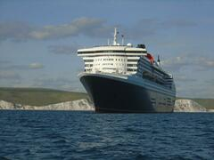 Queen Mary 2 with the Jurassic coast behind